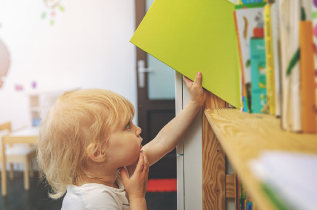 Nen col·locant un llibre a una biblioteca