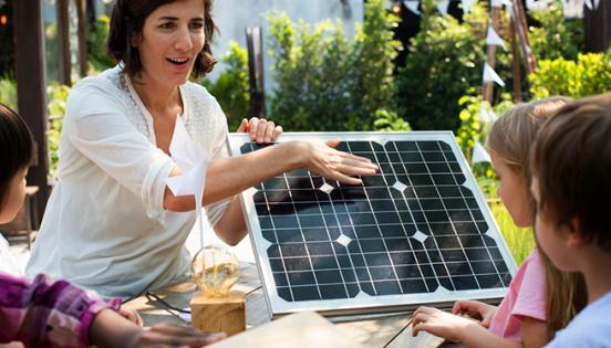 Mestra explicant el funcionament d'una placa solar als nens i nenes