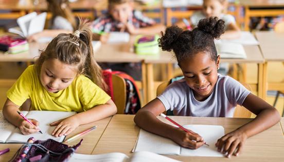Dues nenes de diferents ètnies assegudes juntes a classe
