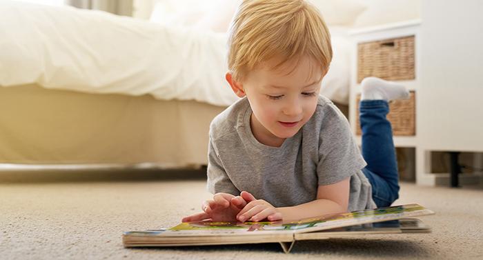 Nen estirat a terra llegint un conte