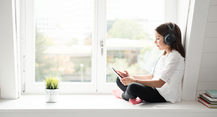 Nena llegeix amb els auriculars posats al costat de la finestra