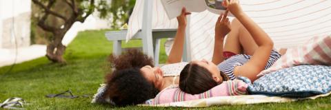 Mare i filla llegint juntes a la gespa