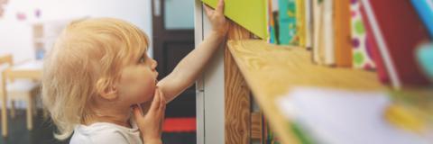Nen petit dubta com col·locar un llibre a una prestatgeria