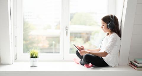 Nena asseguda al costat d'una finestra llegeix a una tablet