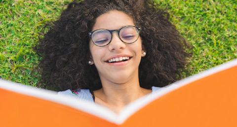Noia llegeix un llibre estirada a la gespa