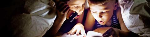 Dos nens llegint al llit a les fosques amb una llanterna