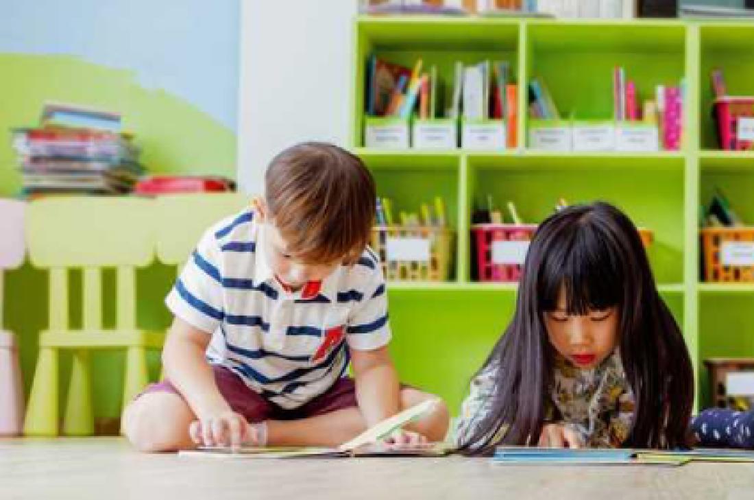 Nens llegeixen al terra d'una aula