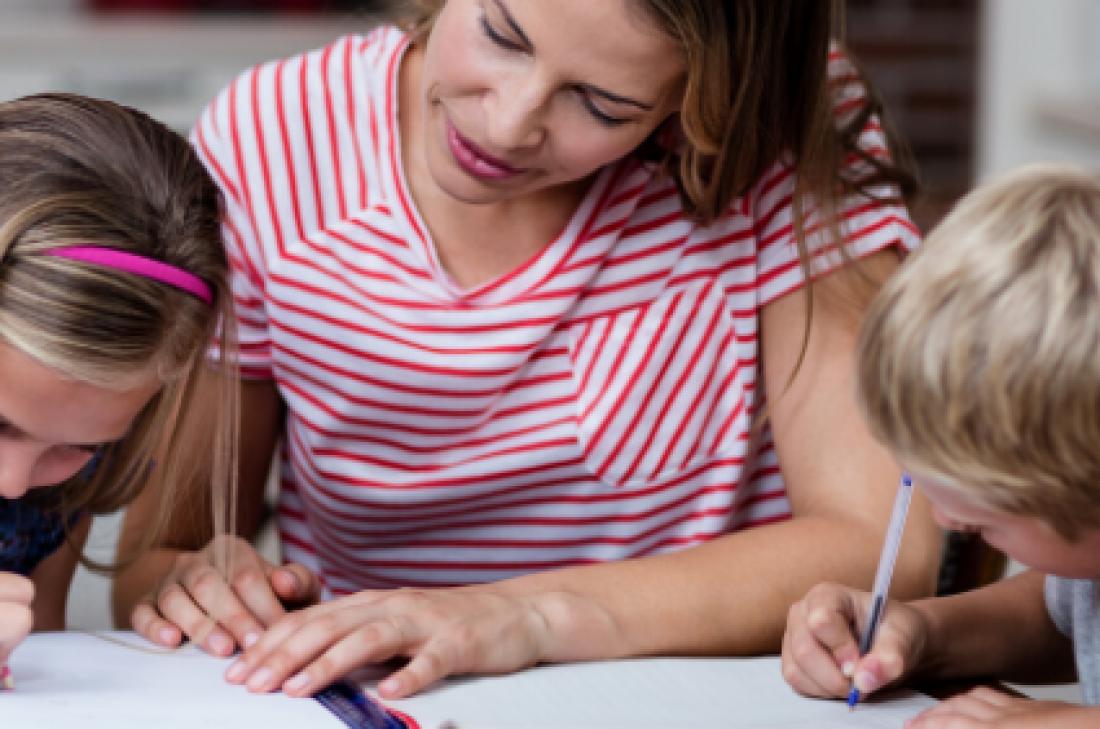 Nen i nena fent deures amb la seva mare a casa