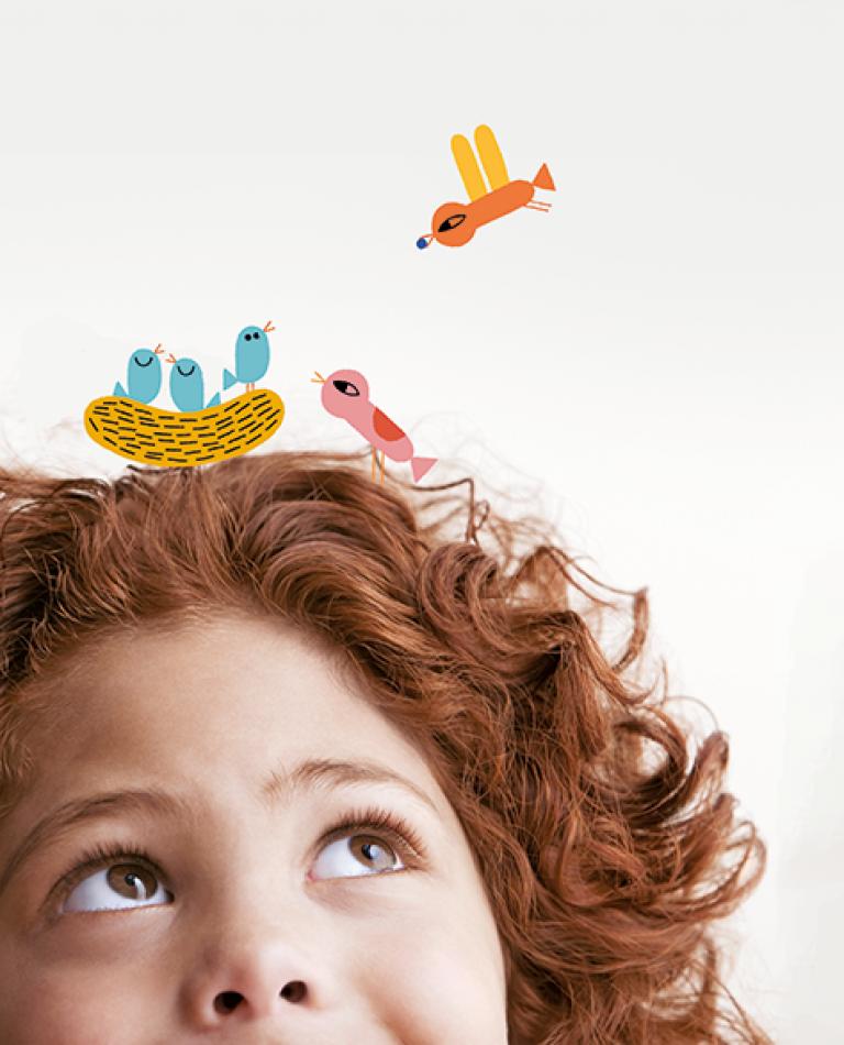 Nena mira uns ocellets il·lustrats en dibuix sobre ella